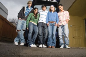 Group of teens looking relaxed by car