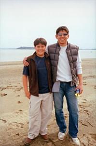 Beach bonding, male carer on beach with teen boy