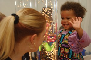 Happy child and carer looking at bubble toy display