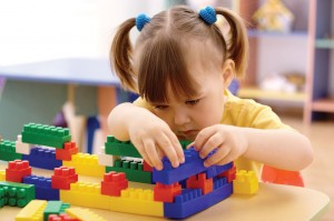 Small child playing with building blocks