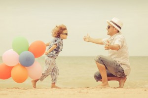 Carer and child on beach with balloons in open embrace