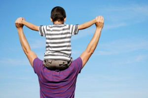 Carer with foster son on his shoulders and clear blue sky