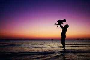 Man holding small child in air on the beach at sunset