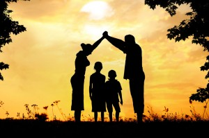 Foster family making a house shape from arms with children below, outside with beautiful sunset