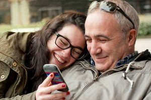 Teen and foster carer looking at mobile phone and laughing
