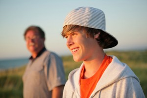 Happy teen with cap on backwards, outside with carer in background