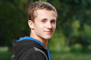 Teen boy looking towards camera, smiling