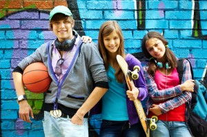 Teens with basketball and skateboards leaning against bright graffitied wall, smiling